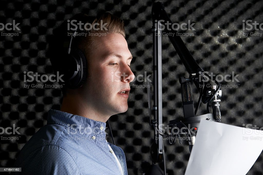 A man in a recording studio speaking into a microphone stock photo