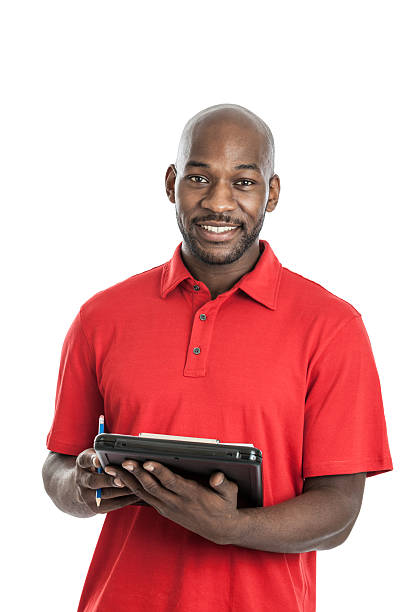 A man in a red polo writing on a clipboard stock photo