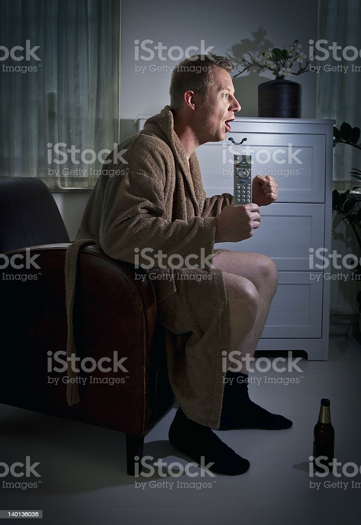 Man in a robe watching the game in a dimly lit room royalty-free stock photo