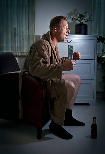man in a robe watching the game in a dimly lit room - dimly stock pictures, royalty-free photos & images
