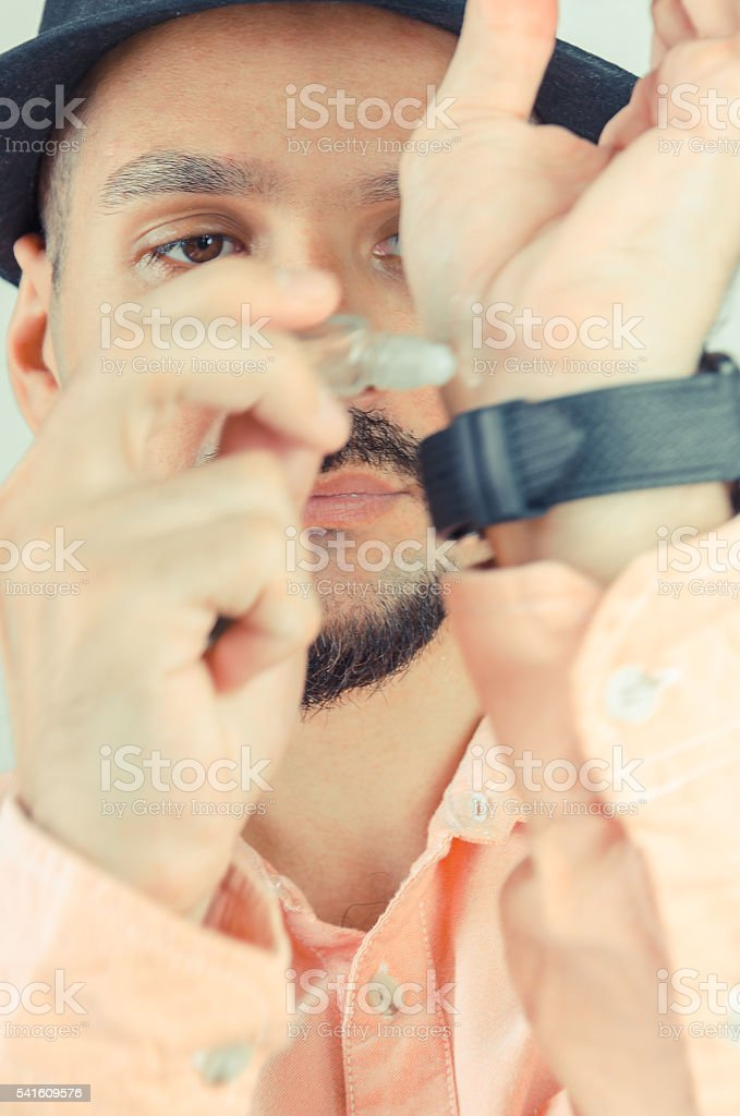 man in a shirt and a hat puts perfume stock photo