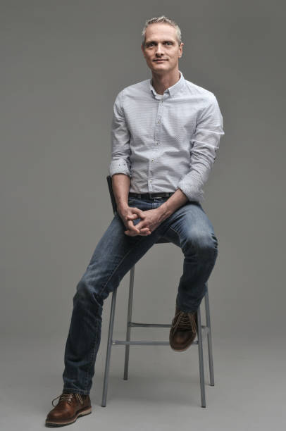 Man in a shirt and jeans is sitting on a chair. Gray background. stock photo