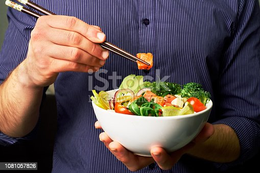 istock man in a shirt holds poke bowl with salmon, avocado, cucumbers, arugula, broccoli, rice, carrots, cheese and chuha with chopsticks 1081057826