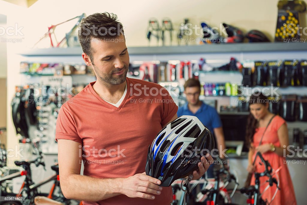 Man in a sports store buying bike helmet stock photo