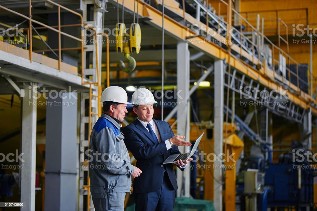 Man in a suit and a worker in overalls The man in the suit and the helmet holds the portable computer and shows up on the screen to the worker in overalls in an industrial building Adult Stock Photo