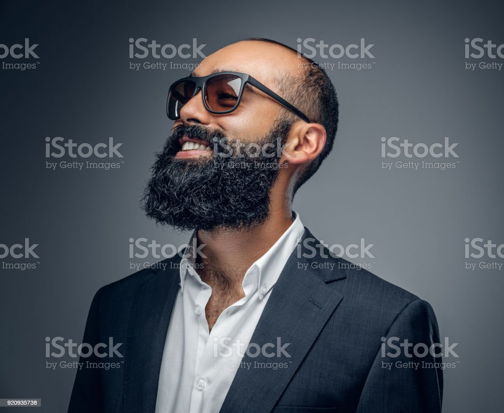 A man in a suit and sunglasses isolated on grey background. stock photo