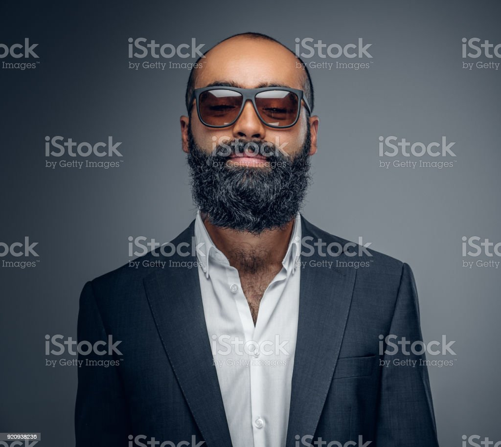 b92699465b22 A man in a suit and sunglasses isolated on grey background. - Stock image .