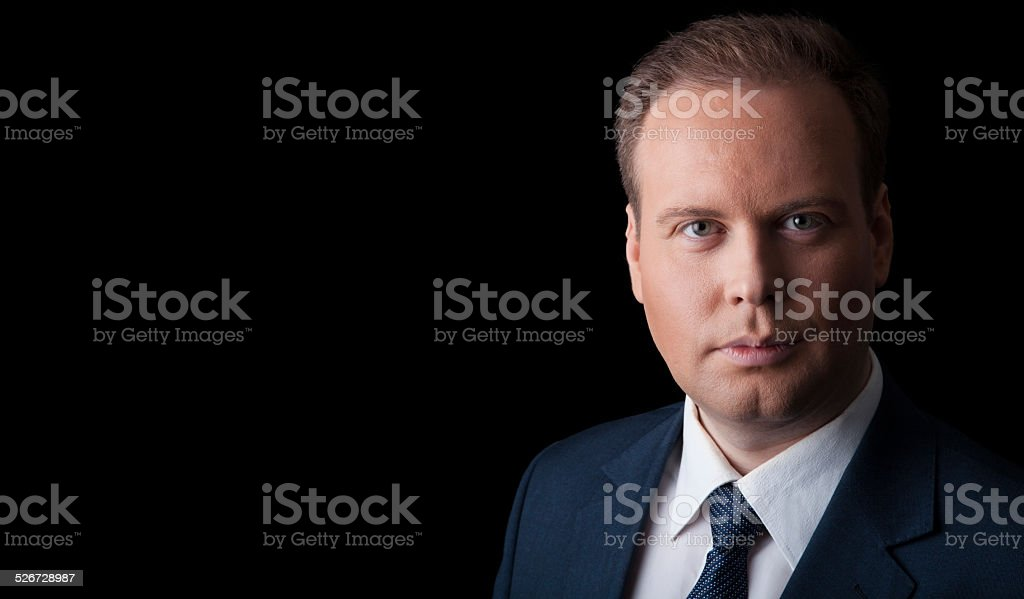 man in a suit and tie on a black background stock photo