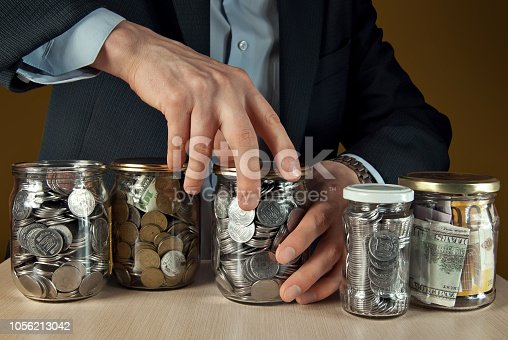 A man in a suit conserved money in glass jars. The concept is the storage of money, stocks at difficult times. Conserve money instead of vegetables.