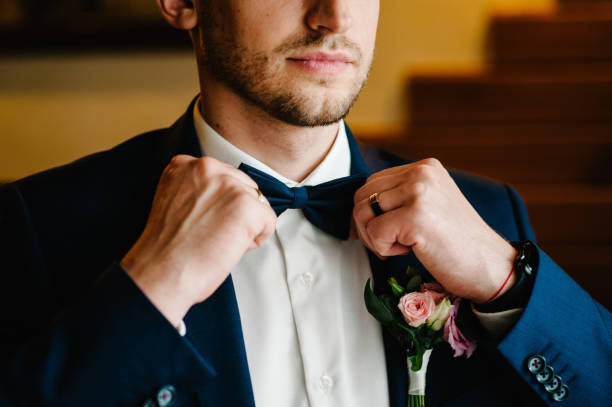 Man in a suit correcting his bow-tie. Morning preparation groom at home. Fashion photo of a man.