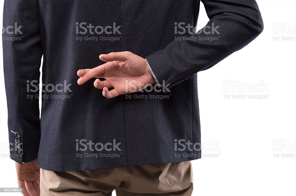 Man in a suit crossed his fingers behind his back stock photo