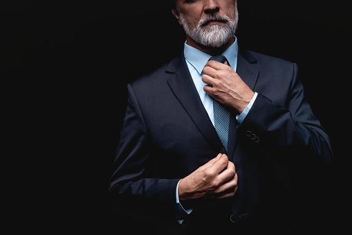 istock Man in a suit fixing his tie. 1075459760