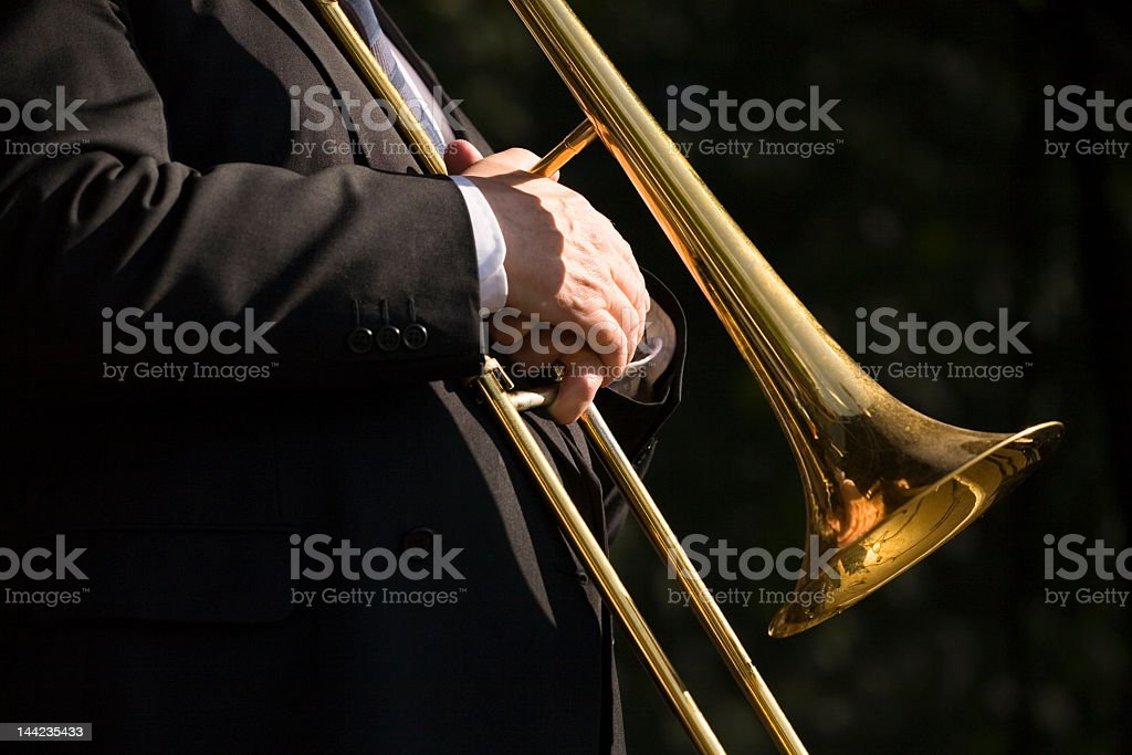 A man in a suit holding a musical instrument stock photo