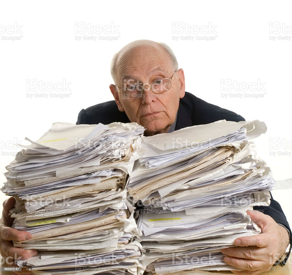 A man in a suit holding two large stacks of paperwork royalty-free stock photo
