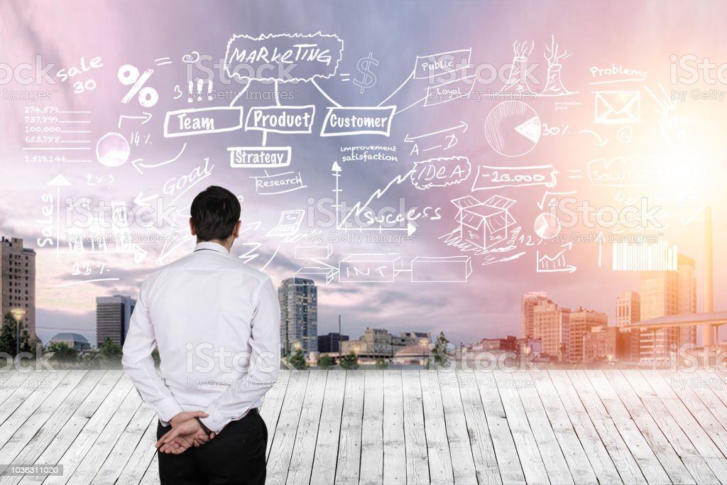Man in a suit looking at business plan projected on a sky above modern city stock photo