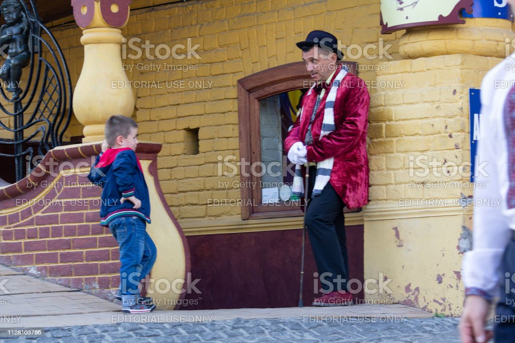 Man in a suit of a famous literary character works for a restaurant talking to a boy on Andriyivsky Descent