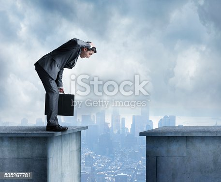 A businessman, holding a briefcase, stands on the ledge of a building. There is another building opposite of him with a gap in between the two. He is leaning over with his mouth open wide and his hand on his head. A big city skyline is in the distance obscured by clouds.