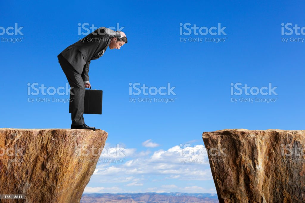 Man in a suit stares at space between two ledges stock photo