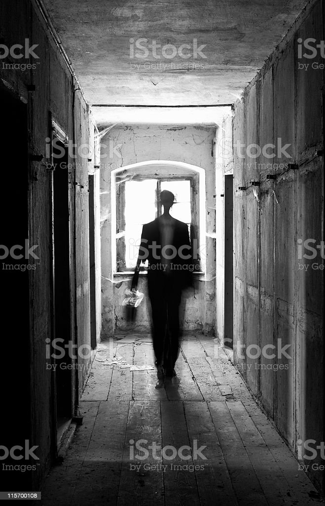 Man in a suit walking down a hallway in black and white stock photo