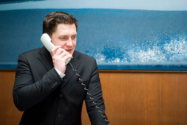 A man in a suite walking on a landline phone Staff at reception in hotel concierge stock pictures, royalty-free photos & images
