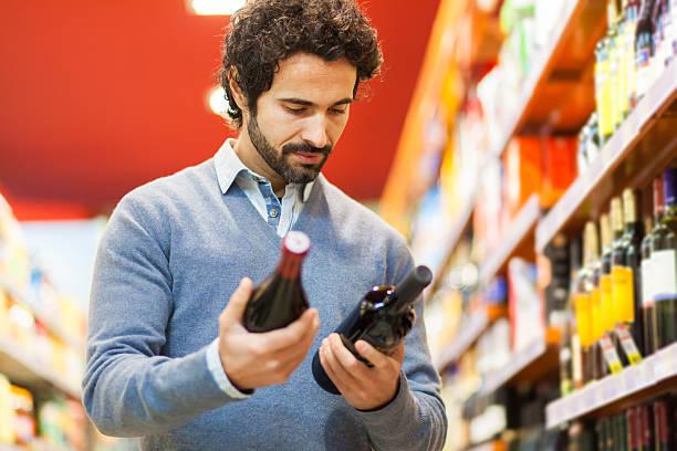 Man in a supermarket choosing wine bottle stock photo