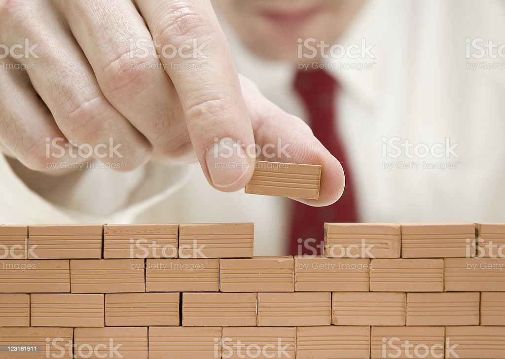 Man in a tie adds tiny clay brick to a wall of tiny bricks stock photo