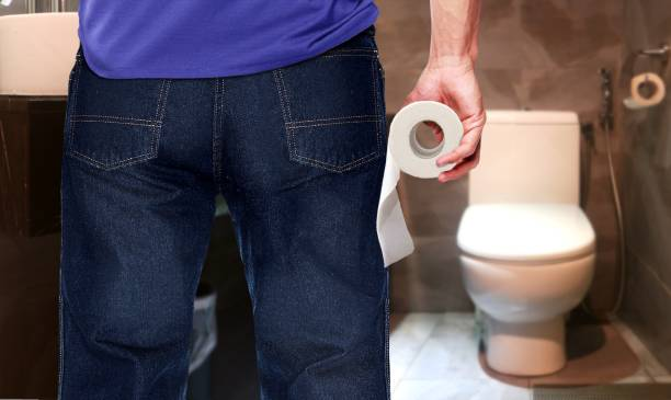 Man in a toilet holding tissue paper roll stock photo