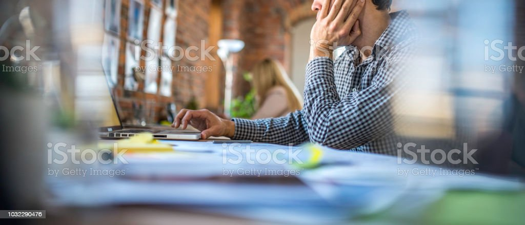 Man in a trendy office Unrecognisable man sitting  behind a desk in modern office. Adult Stock Photo
