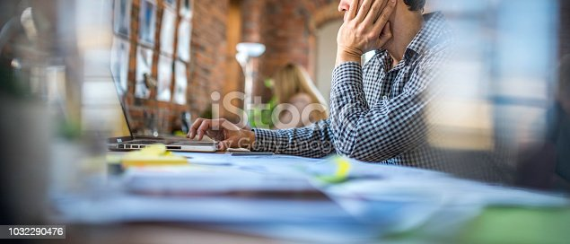 Unrecognisable man sitting  behind a desk in modern office.
