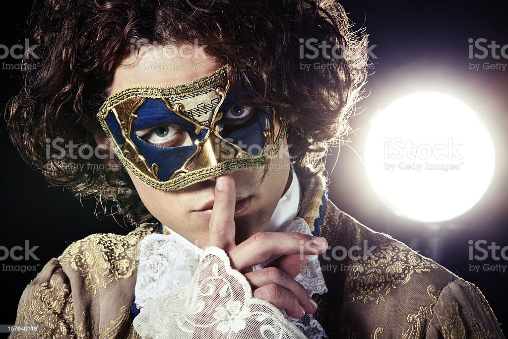 A man in a Venetian mask putting a finger to his mouth stock photo