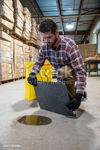 A man in a warehouse putting an absorbent mat on a puddle of oil.