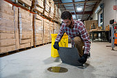 A man in a warehouse putting an absorbent mat on a puddle of oil.  He is using a spill response kit.
