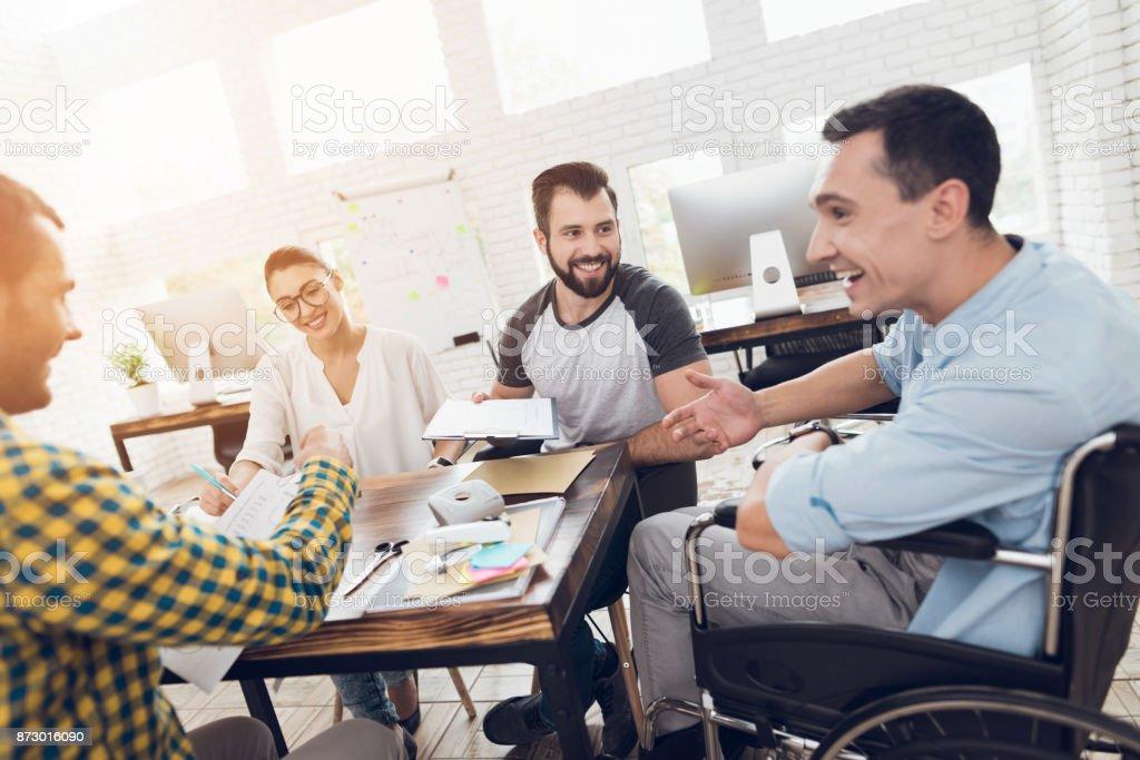 Un hombre en silla de ruedas se comunica con alegría con empleados de la oficina durante una reunión de negocios. - foto de stock