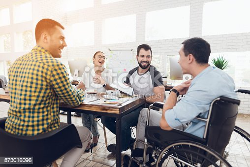 istock A man in a wheelchair communicates cheerfully with employees of the office during a business meeting. 873016096