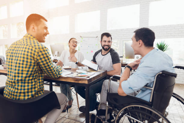 A man in a wheelchair communicates cheerfully with employees of the office during a business meeting. Office workers and man in a wheelchair are making a conversation in bright office. They are showing a teamwork. persons with disabilities stock pictures, royalty-free photos & images
