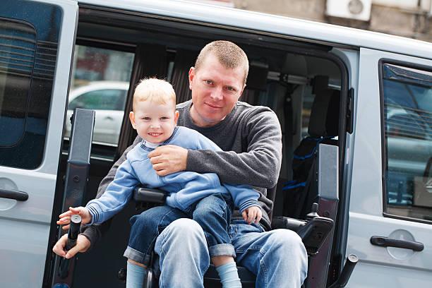 Ein Mann im Rollstuhl mit einem Kind – Foto
