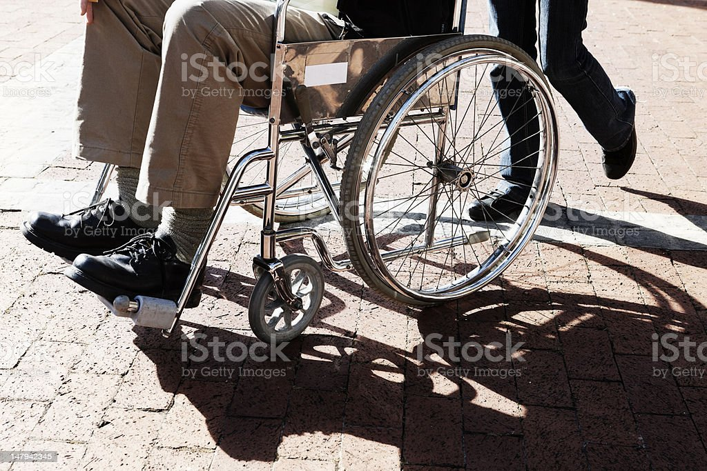 Man in a wheelchair is pushed across parking lot royalty-free stock photo
