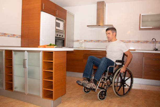 A man in a wheelchair moves through the kitchen stock photo