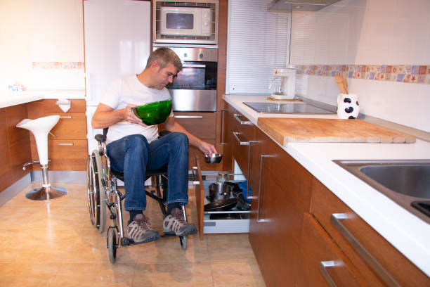 A man in a wheelchair preparing food in the kitchen stock photo