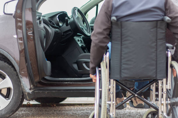A man in a wheelchair trying to get into the driver's seat of a car stock photo