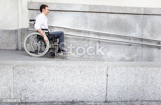 istock Man in a wheelchair using accessible ramp 470893873