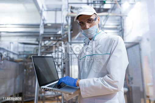 685555238 istock photo man in a white robe and a mask with a laptop in his hands is at the factory 1133394825