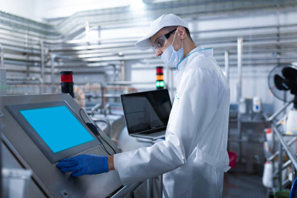 man in a white robe and a mask with a laptop in his hands stands near the digital screen at the factory stock photo