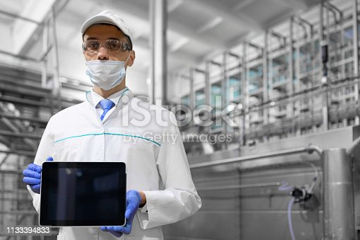 685555238 istock photo man in a white robe and a mask with a tablet in his hands is at the factory 1133394833