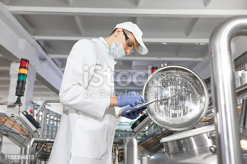 685555238 istock photo man in a white robe and a mask with a tablet in his hands is near can in the shop 1133394813