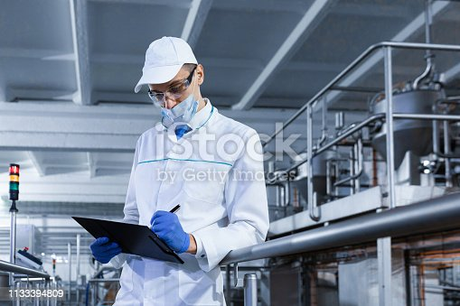 685555238 istock photo man in a white robe and mask makes notes standing in the shop 1133394809