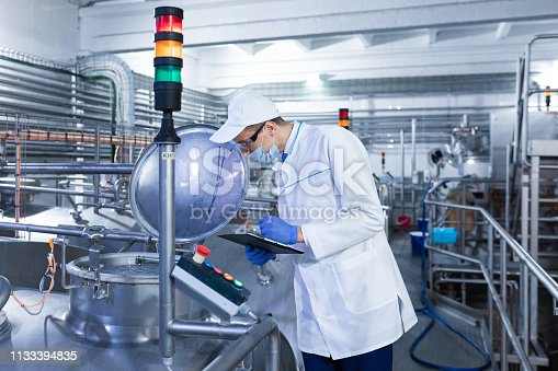 685555238 istock photo man in a white robe and mask makes notes standing in the shop 1133394835