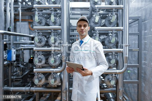 685555238 istock photo man in a white robe with a tablet in his hands is in the production shop at the factory 1133394776