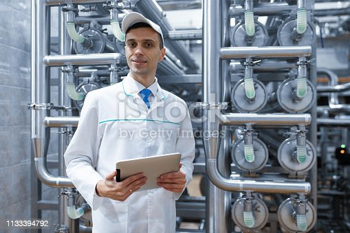685555238 istock photo man in a white robe with a tablet in his hands is in the production shop at the factory 1133394792