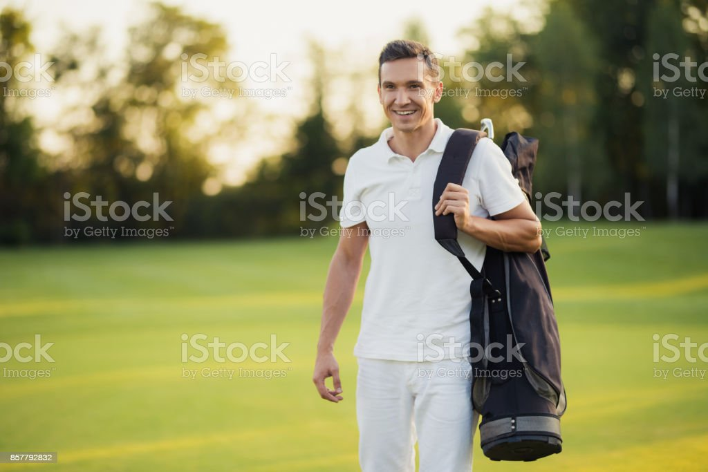 A man in a white T-shirt and white trousers is walking along the golf...